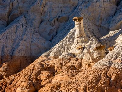 White and Chocolate Hoodoos Against Blue Cliffs